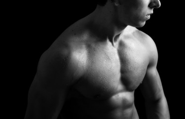 Muscular young man on black background,  black-and-white edition