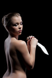 Nude young woman with knife in dark