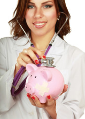 A doctor listening piggy box with a stethoscope, close-up
