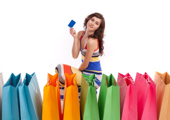 A girl sitting next to a shopping bag with a credit card