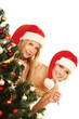Two girlfriends in santa hat standing near Christmas tree