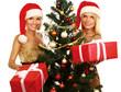 Two girlfriends in santa hat near Christmas tree