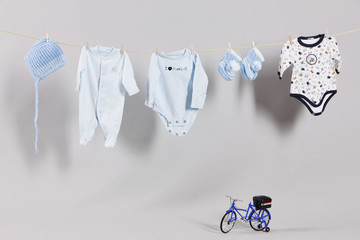 Baby boy clothes, hat and slippers on a clothesline.