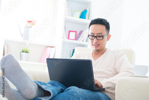 Asian male using internet at home