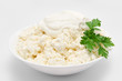 Cottage cheese in the bowl with sour cream and parsley isolated