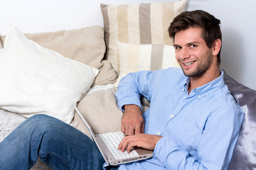 Young man using laptop on couch