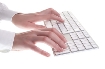 Hands typing on white computer keyboard