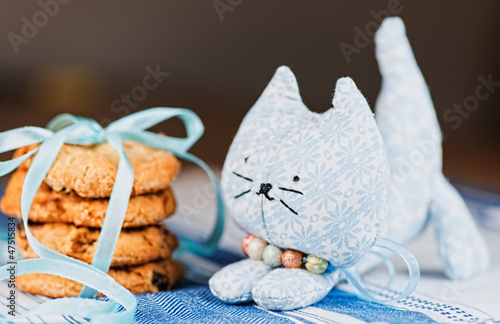 Homemade toy cat and cookie on tablecloth