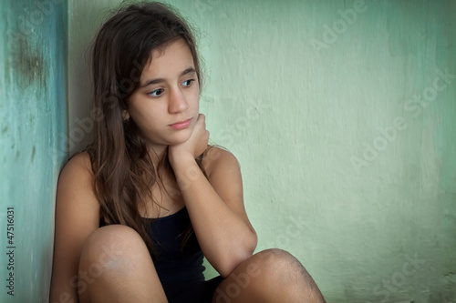 Sad and lonely hispanic girl sitting in a corner