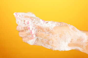 Woman's hands in soapsuds, on orange background close-up
