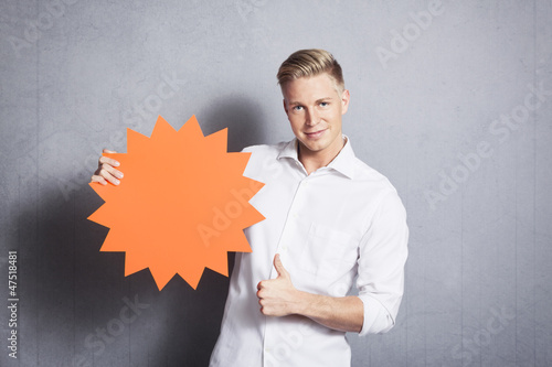 Man giving thumbs up at empty sign promoting sales.