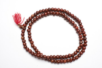 Prayer beads made from sandalwood in a white background