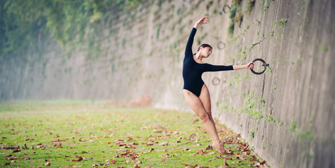 Young beautiful ballerina dancing on Tevere riverside in Rome.