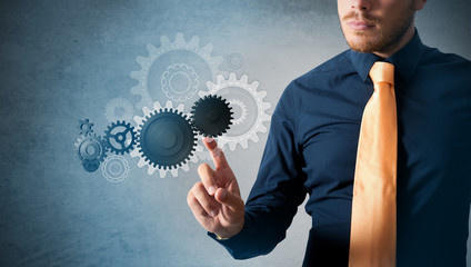 Businessman and virtual interface with cogwheels