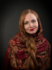 Smiling Slavonic girl with red braided hair, dark background