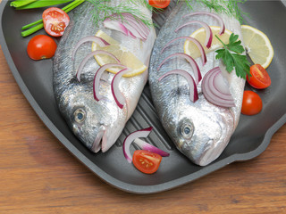 Dorado fish, lemon and vegetables in a pan