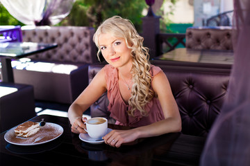 Beautiful blonde girl posing sitting in a cafe