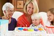 Family Celebrating Children's Birthday With Grandmother