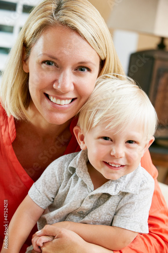 Portrait Of Mother And Son Sitting On Sofa At Home