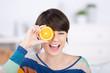lachende frau mit orangenscheibe