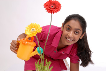 Young girl watering plant