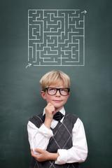 Kind vor der Tafel mit Labyrinth