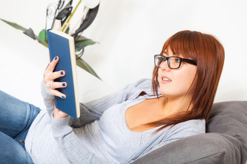 Beautiful Young Woman with a Book on the Sofa