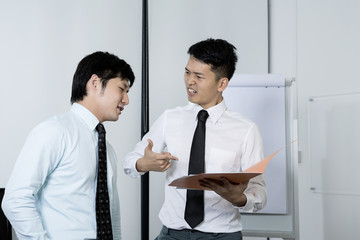 Two stressed Chinese businessmen reading a file