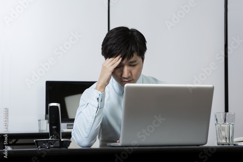 Chinese businessman holding his head