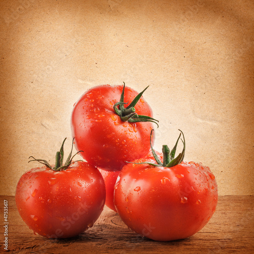 Tomatoes on the grunge yellow paper background