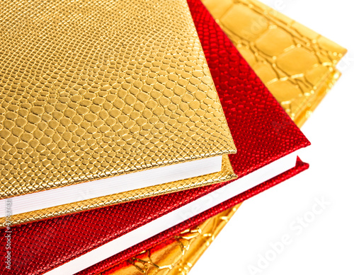 Golden and red notebooks isolated