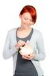 rothaariges mädchen wirft 10 euro ins sparschwein