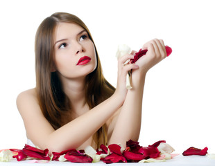 The beautiful girl with petals of roses isolated