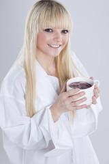 junge blonde Frau ist glücklich mit ihrer Tasse Tee in der Hand