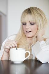 junge blonde  Frau am gähnen vor Müdigkeit mit Tasse Kaffee