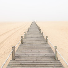 Passerelle en bois sur une plage de sable brumeux. Portugal.