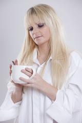 junge blonde Frau mit Tasse Kaffee in der Hand