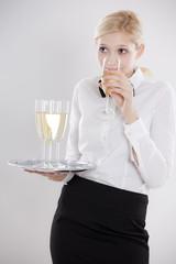 junge Kellnerin trinkt selbst heimlich ein Glas Sekt