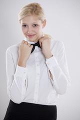 junge blonde Frau mit Bluse und Fliege