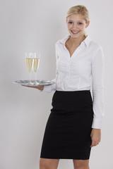 Freundliche Kellnerin mit Sektgläsern auf dem Tablett