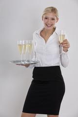 freundliche Kellnerin Azubi bietet ein Glas Sekt an
