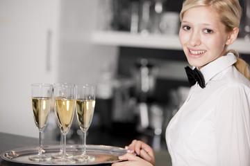 freundliche junge Kellnerin mit Fliege und Sektgläsern