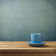 Blue coffee cup on wooden table over blue grunge background
