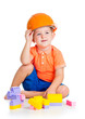 cheerful child boy with hard hat playing with building blocks to