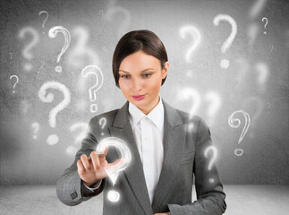 Business woman with question symbols around her. Choosing one an