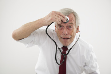 Senior man holding a stethosope to his forehead