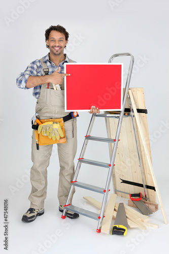 woodworker holding a painted ad board