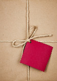 Gift with red tag in brown paper