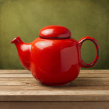 Red tea pot on wooden table over green grunge wall