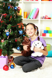 Little girl holding toys near christmas tree